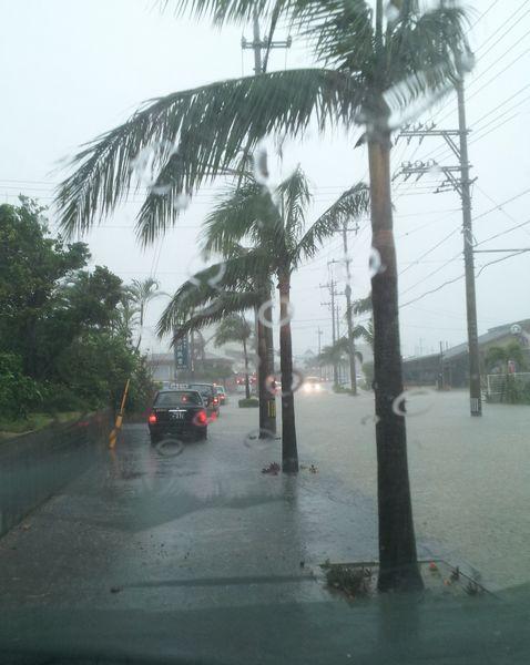 道路冠水のため、歩道を車が走っています。